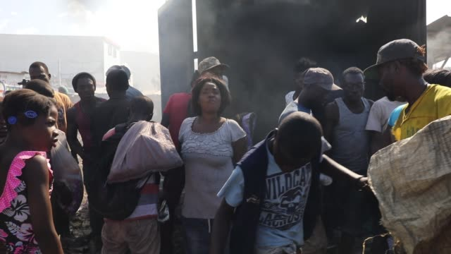haitians desperately try to get into a burning shipping container to salvage clothes during a fire at portauprince's historic iron market on february... - insel hispaniola stock-videos und b-roll-filmmaterial
