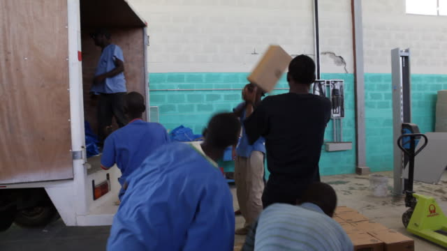 haitians unload earthquake relief supplies from a truck. - emergencies and disasters stock videos & royalty-free footage