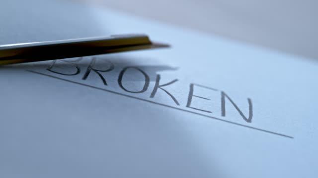 """slo mo ld half a broken pencil flying across the inscription """"broken"""" - broken pencil stock videos & royalty-free footage"""