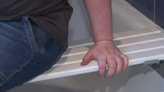 half a million disabled people face cuts to benefits england int various of multiple sclerosis sufferer bethen thorpe lifting wooden bath mat out of... - disability benefits stock videos & royalty-free footage