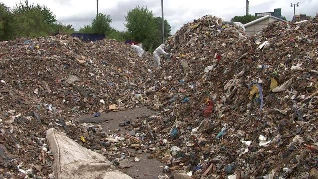 half a million pounds needed to clean up 800 tonnes of rubbish dumped in woolwich england london woolwich ext man putting on protective clothing... - rubbish stock videos and b-roll footage