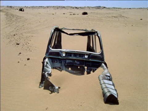 vídeos de stock e filmes b-roll de half buried shell of wrecked vehicle in soft desert sand sahara desert - chassi