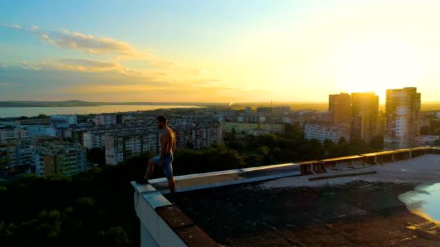 vídeos y material grabado en eventos de stock de medio círculo drone tiro de un hombre de pie en el borde de un techo de construcción de la ciudad - tejado