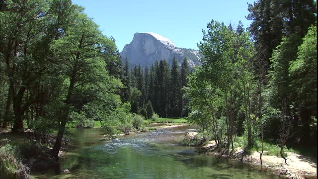 vídeos de stock, filmes e b-roll de half dome peak looms above a gently flowing river in yosemite national park. - condado de mariposa