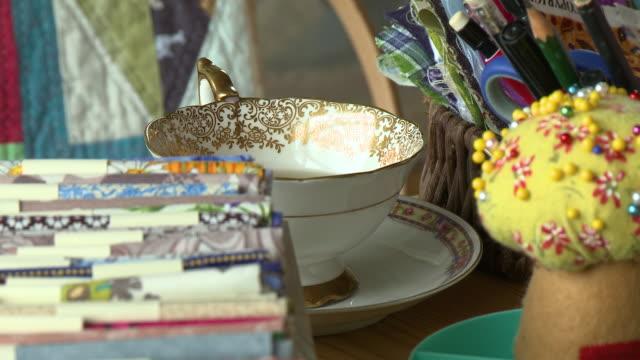 half full tea cup on craft table - folded stock videos & royalty-free footage