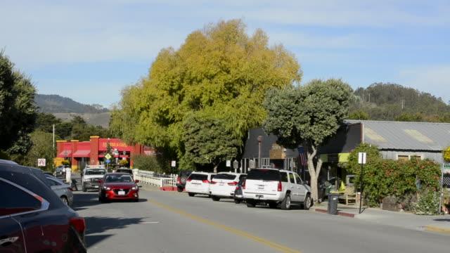 Half Moon Bay California downtown Main Street road traffic Half Moon Bay Feed & Fuel Co pink building at end of street