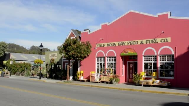 Half Moon Bay California downtown Main Street road traffic Half Moon Bay Feed & Fuel Co pink building