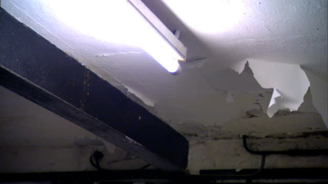 half of bare fluorescent light bulb coming on dim then on full pulsing ceiling w/ open wood beam paint peeling hanging down light going out darkness - fluorescent light stock videos & royalty-free footage