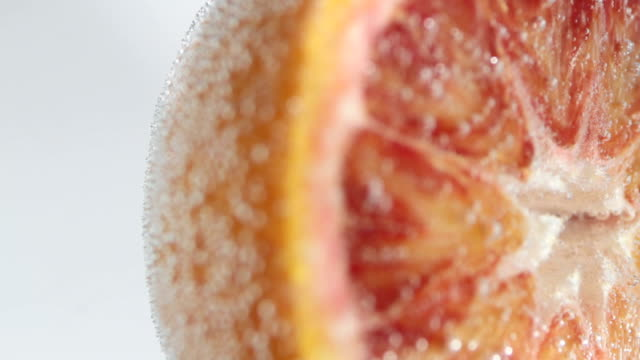 Half of blood orange in sparkling water