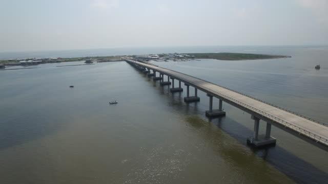 Half orbit around bridge - Drone Aerial 4K Grand Isle Louisiana coast Mississippi river bridge and barge 1of14, everglades, gulf delta, with boats sailing and wildlife 4K Transportation