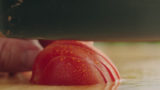 CU Half organic tomato on kitchen chopping block, sliced with steel knife / Los Angeles, California United States