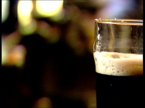 half pint of lager beer on bar side pint of guinness emptying professor john henry interview sot - in the long run it may mean that we have new ways... - pint stock-videos und b-roll-filmmaterial
