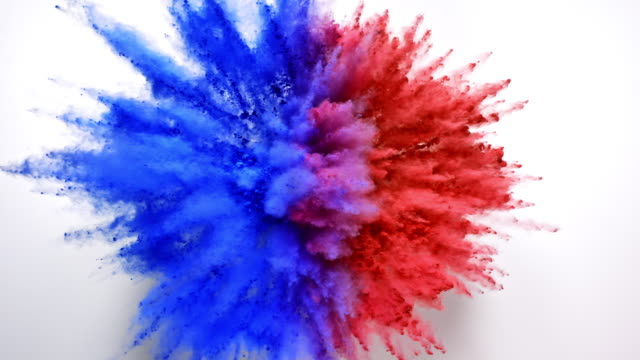 half red and half blue colored powder exploding towards camera in close up and super slow-motion, white background - exploding stock videos & royalty-free footage