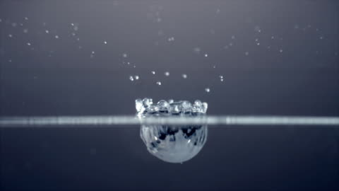 half submerged slow motion shot of a single white droplet falling into water and bouncing off the surface - impact stock videos & royalty-free footage