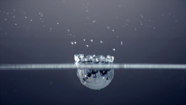 Half submerged slow motion shot of a single white droplet falling into water and bouncing off the surface