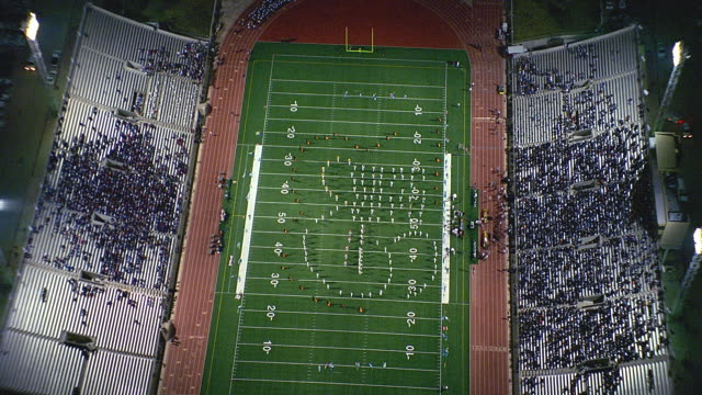 aerial half time show at high school football game at night / odessa, texas - game show stock videos & royalty-free footage
