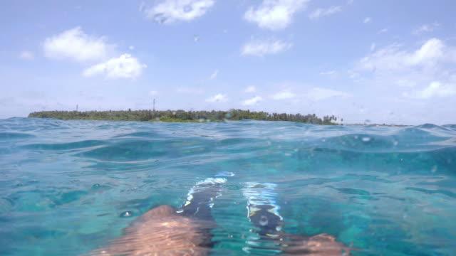 stockvideo's en b-roll-footage met half onderwater foto-pov uitzicht van benen met vinnen in een paradijselijke zee in de malediven - zwemvlies