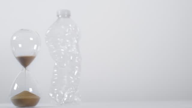 vídeos de stock e filmes b-roll de half-full sand timer next to plastic bottle 2 - utilização única