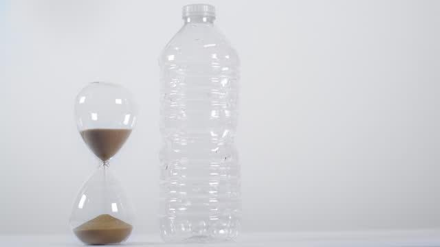 vídeos de stock e filmes b-roll de half-full sand timer next to plastic bottle on white background - utilização única
