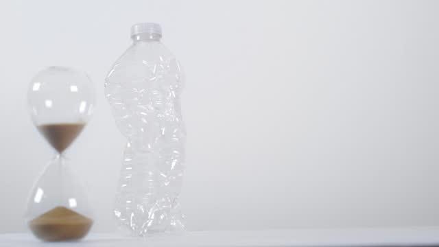 vídeos de stock e filmes b-roll de half-full sand timer next to plastic bottle - utilização única