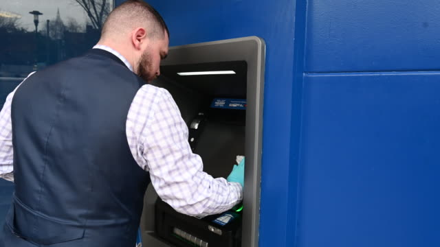 halifax bank worker cleans a cash point on march 18 in cardiff, wales. the coronavirus pandemic has spread to many countries across the world,... - hygiene stock videos & royalty-free footage