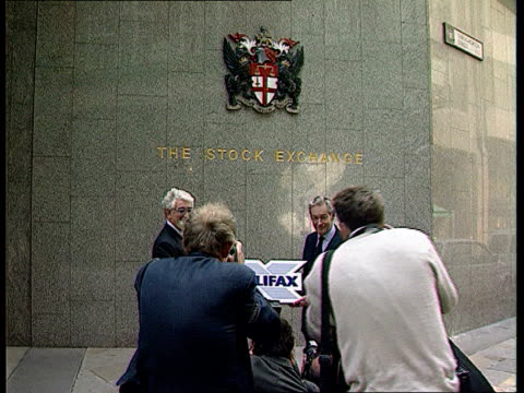 halifax shares begin trading itn london the stock exchange mike blackburn and halifax chmn along and pose under 'the stock exchange' sign as... - inn stock videos and b-roll footage