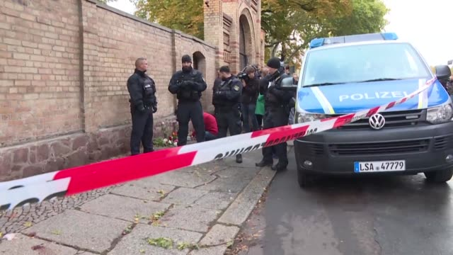 halle residents and synagogue worshippers gather in front of the building after two people were shot dead in an attack carried out on the holy day of... - jom kippur stock-videos und b-roll-filmmaterial