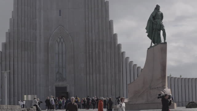 hallgrímskirkja cathedral on the horizon while people and cars crossing on this establishing shot in reykjavik - architecture stock videos & royalty-free footage