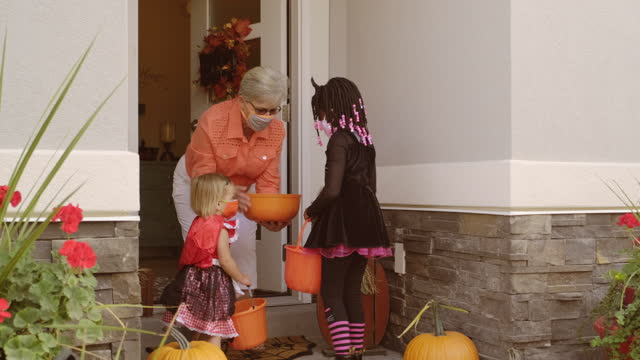 halloween children trick or treating wearing facemasks - halloween stock videos & royalty-free footage