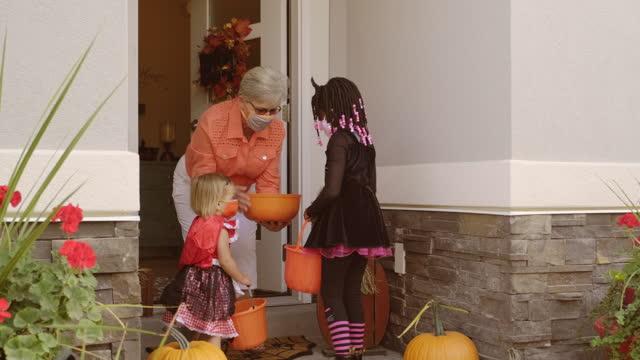 halloween-kinder trick oder behandlung tragen gesichtsmasken - halloween stock-videos und b-roll-filmmaterial
