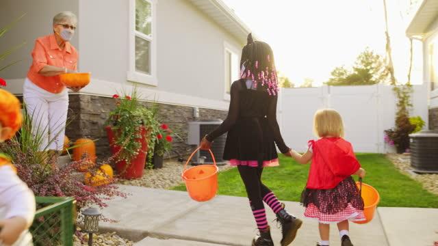 ハロウィーンの子供たちは、フェイスマスクを着用してトリックまたは治療 - 菓子類点の映像素材/bロール