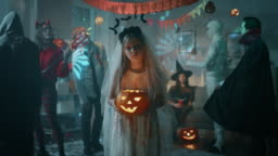 Halloween Costume Party: Little Girl in a Bloody White Bride Dress Holding Scary Doll. Zombie, Blood Thirsty Dracula, Mummy, Bewitching Witch and Dazzling She Devil Having Fun in Decorated Room