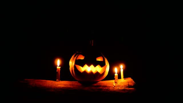 vídeos y material grabado en eventos de stock de halloween jack o lantern con velas sobre el tronco de árbol en la oscuridad, tiro de carro - calabaza no comestible