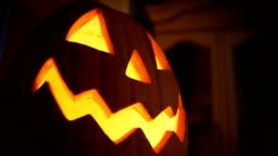 A Halloween Jack-O-Lantern Pumpkin lights up inside a home