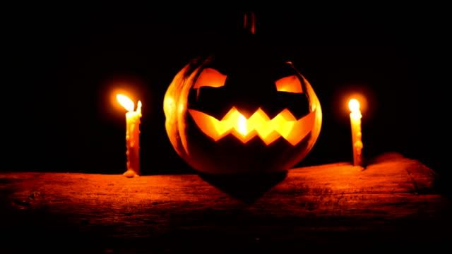 vídeos y material grabado en eventos de stock de halloween calabaza brillante con velas sobre el tronco de árbol en la oscuridad, tiro de carro - calabaza no comestible