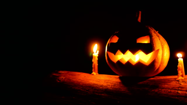 halloween pumpkin glowing with candles on tree trunk in the dark, dolly shot - zucca legenaria video stock e b–roll