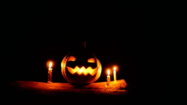vídeos y material grabado en eventos de stock de calabaza de halloween jack-o-linterna con velas sobre el tronco de árbol en la noche, tiro de carro - calabaza no comestible