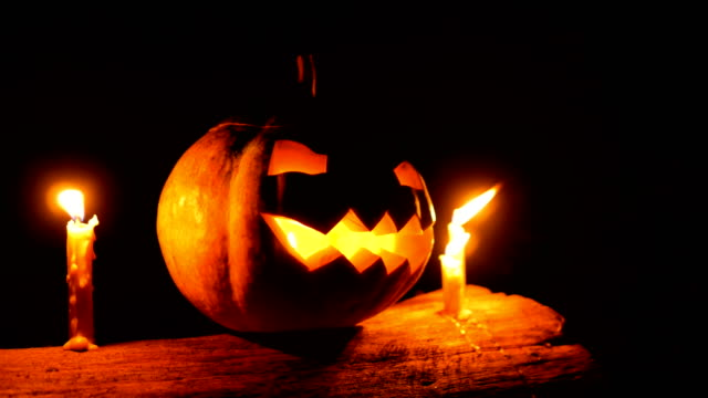 halloween pumpkin jack-o-lantern with candles on tree trunk in the night, dolly shot - zucca legenaria video stock e b–roll