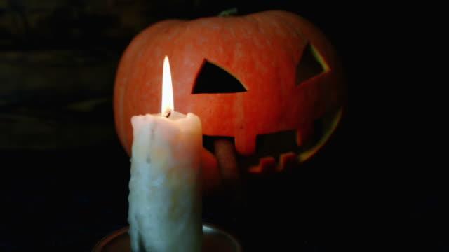 halloween. pumpkin mask, smokes a cigar. the candle burns - halloween wallpaper stock videos and b-roll footage