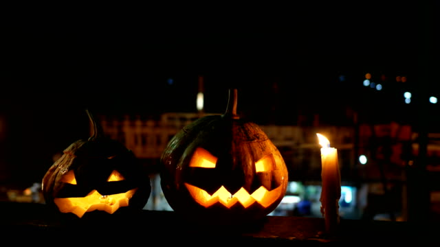 vídeos de stock e filmes b-roll de halloween pumpkins jack-o-lantern with candles in the night with traffic background, dolly shot - lagenaria