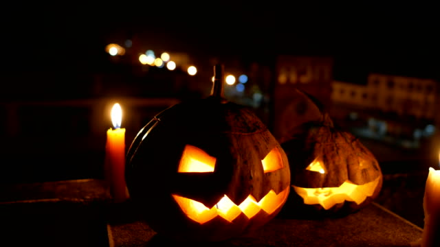 vídeos y material grabado en eventos de stock de calabazas de halloween jack-o-linterna con velas en la noche con el tráfico de fondo, tiro de carro - calabaza no comestible