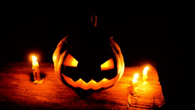 vídeos y material grabado en eventos de stock de halloween calabaza sonriente con velas sobre el tronco de árbol en la oscuridad, tiro de carro - calabaza no comestible