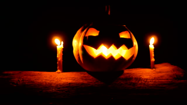 Halloween Smiling Pumpkin with Candles on Tree Trunk in the Dark, Dolly shot