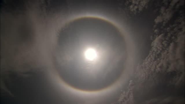 halo around shining sun in blue sky, uganda - halo stock videos and b-roll footage