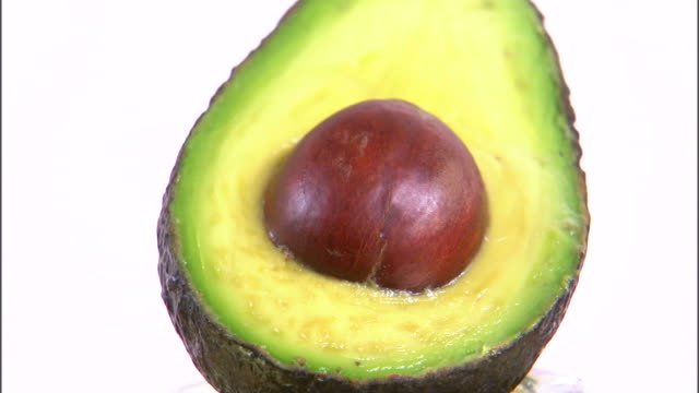 vídeos y material grabado en eventos de stock de cu halved avocado rotating against white background / orem, utah, usa - aguacate