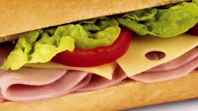 ham, cheese, tomato and lettuce in baguette - ハム点の映像素材/bロール