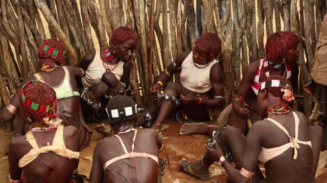 Hamar tribe during the Bull Jumping ceremony The young women are prepering the leg bells for dancing during the Whipping ritual Omo river Ethiopia