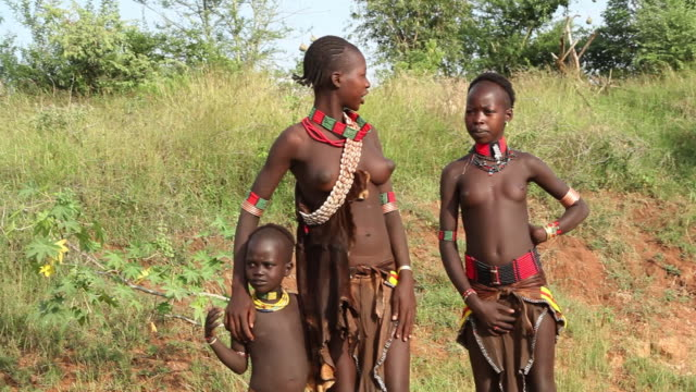 Hamar tribe girls in traditional clothing on their way to the village to watch the Bull Jumping ceremony Omo river Ethiopia