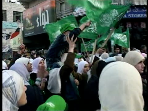 stockvideo's en b-roll-footage met hamas win palestinian elections west bank ramallah hamas supporters celebrating in street zoom in to boy sitting shoulder high waves green flag - startvlag
