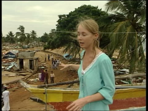 hambantota remains of boats and buildings washed up amongst palm trees pull out to outrigger fishing boat sitting on roof cms woman covering her face... - 2004 stock videos & royalty-free footage